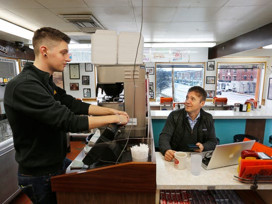 Server Nick Ahlbrand, left, talks with commercial realtor Steve Shook Thursday, January 26, 2017, at Triple XXX Family Restaurant, 2 N. Salisbury in West Lafayette.