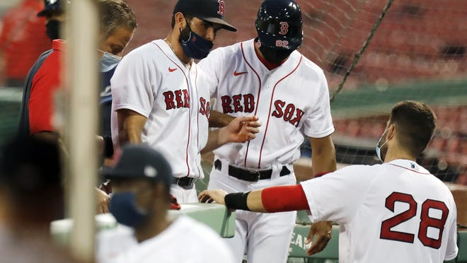 Boston Red Sox infielder Jose Peraza, center left, enters the dug out after being injured while pitching during the ninth inning of Thursday's game against the Tampa Bay Rays in Boston.