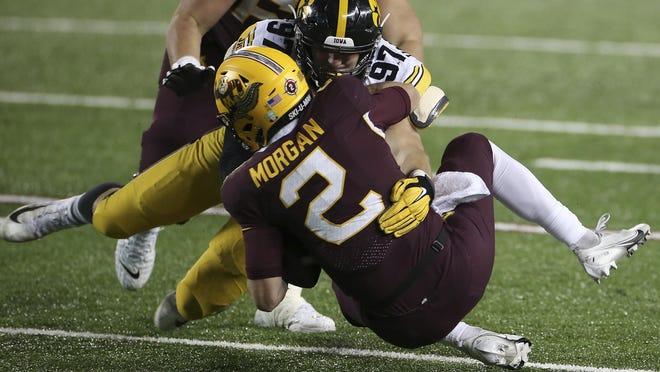 Iowa defensive lineman Zach VanValkenburg (97) sacks Minnesota quarterback Tanner Morgan (2) during the second half of an NCAA college football game Friday, Nov. 13, 2020, in Minneapolis. Iowa won 35-7.
