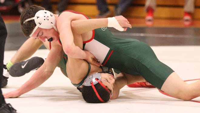 Oak Harbor's Cam Dickman (126) works for a pin.