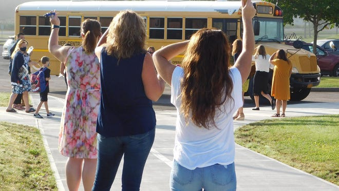 Herkimer Elementary School teachers and staff members greet third through fifth graders arriving by bus Thursday, Sept. 3, 2020, for the first day of school.