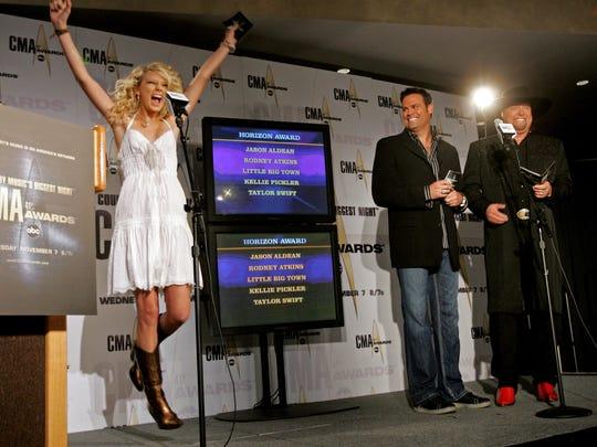 Taylor Swift, left, jumps for joy after Troy Gentry