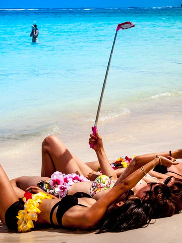 Tourists from Osaka, Japan, taking selfies on a beach