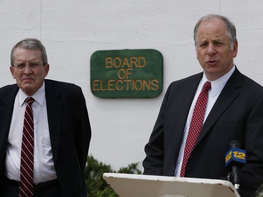 Jeff Bell, left, stands while Richard Pezzullo talks during a news conference, Wednesday, June 4, 2014, in Freehold, N.J. (AP Photo/Julio Cortez)