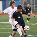 Livonia  Franklin defender Nolan Hannis (left) battles toe-to-toe with Wayne Memorial's Sean Royal during Tuesday night's KLAA South Division clash.