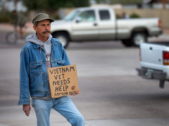 Stephen Quick, 60, panhandles on the corner of Apache and Price, in Tempe, on October 18, 2014. Quick is trying to raise $45 for a night in a hotel room. He says he doesn't like the shelter.
