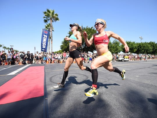 Talayna Fortunato, left, of Naples finishes a three-mile run, following 300 double-under jump ropes and a 3,000-meter row during the Triple 3 event of the CrossFit Games on Friday in Carson, Calif.
