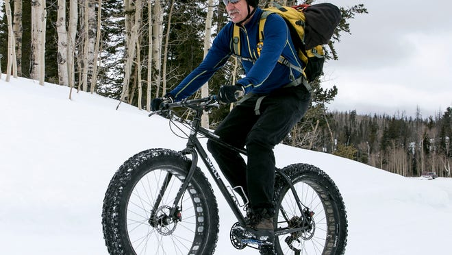 Topher Mason riding his Surly snow bike around Deer Valley up in Cedar Canyon. The wider tires on these fat bikes give better grip and allow bike enthusiasts another option for winter recreation.