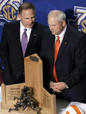 LSU coach Les Miles, left, and Tennessee coach Phillip Fulmer pose with the SEC championship trophy in Atlanta on Friday, Nov. 30, 2007.