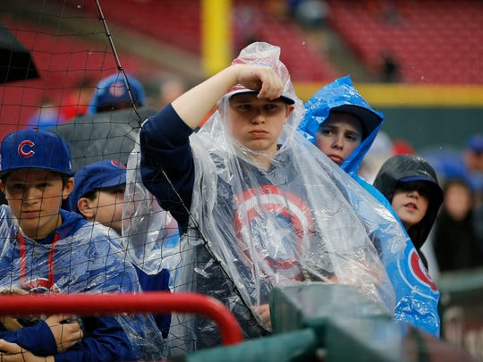 Young Cubs fans peer into the visitors dugout during a rain delay before the first inning of the MLB National League game between the Cincinnati Reds and the Chicago Cubs at Great American Ball Park in downtown Cincinnati on Tuesday, April 3, 2018.