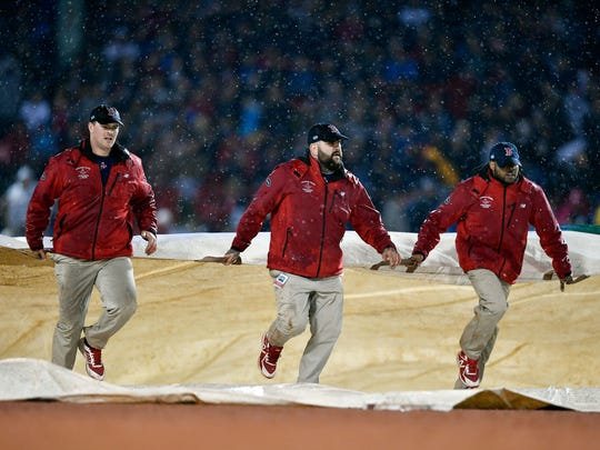 Grounds crew pull out a tarp to cover the infield after