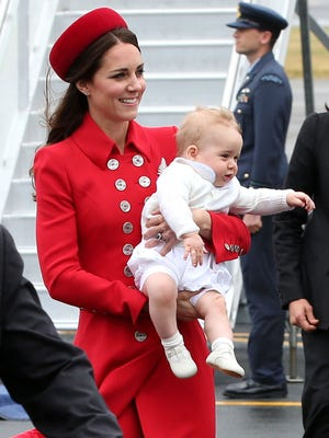It's wet and windy in Wellington when Prince George comes down the stairs of the jet with his mother, dressed in a creamy white sweater and booties. She's in a scarlet Catherine Walker coat with a matching ring-shaped hat by Gina Foster and a silver and platinum leaf-shaped brooch borrowed from the queen.