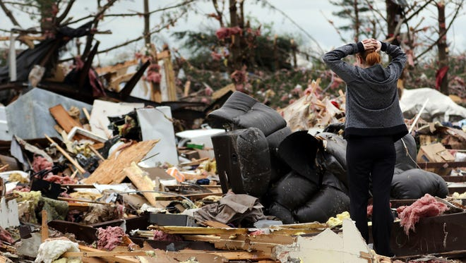 Marissa Rhoades searches for her missing cat at the Prairie Lake Estates mobile home park in Barron County, Wis. Residents of an Oklahoma subdivision and a Wisconsin trailer park that were leveled by deadly tornadoes sifted through what remained of their homes and possessions.