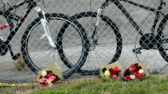 Flowers are placed near unretrieved bicycles outside the Marjory Stoneman Douglas High School in Parkland, Fla., on Feb. 18, 2018,  where 17 people were killed in a mass shooting.  Authorities opened the streets around the school, which had been closed since the shootings. Nikolas Cruz, a former student, was charged with 17 counts of premeditated murder.