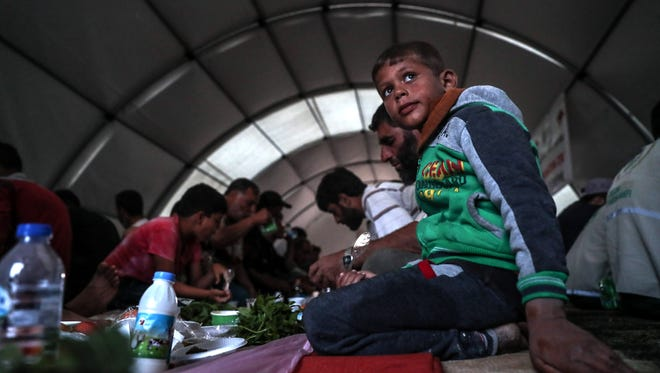 Refugees break their fasting at a camp supported by the Turkish Red Crescent for people who were forcibly displaced from Eastern Ghouta, near al-Bel village, A'zaz city, north of Aleppo's countryside, Syria, on May 22, 2018.