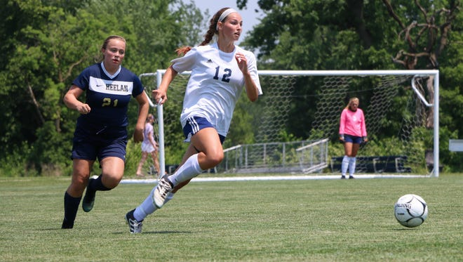 Iowa City Regina's Anna Ziniel (12) is chased by Bishop Heelan's Ellie Barber (21) during the girls' Class 1A state soccer semifinals at the Cownie Soccer Complex in Des Moines on June 8, 2018.