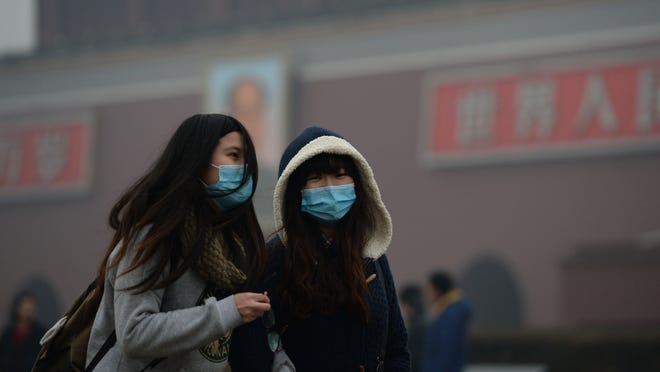 Girls wear masks while walking in haze-covered Tiananmen Square in Beijing on Feb. 23.