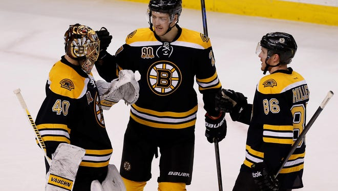 Bruins defensemen Dougie Hamilton, center, and Kevan Miller, right, congratulate goalie Tuukka Rask after defeating the Detroit Red Wings 4-1 on Sunday in Boston.