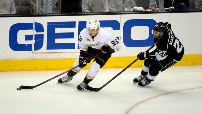 Anaheim Ducks left wing Jakob Silfverberg (33) carries the puck away from Los Angeles Kings defenseman Alec Martinez (27) during the first period in game three of the second round of the 2014 Stanley Cup Playoffs at Staples Center on Thursday.