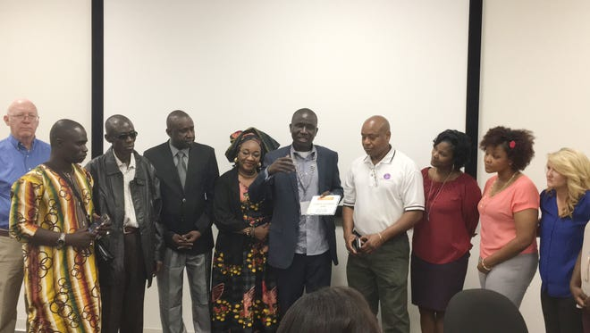 Serigne Ibra Fall, CEO of CAPCA, center, presents an award to Ibrahim Sidibe, president and CEO of Healing Touch Career College, at Fall's left, for his outstanding entrepreneurship.