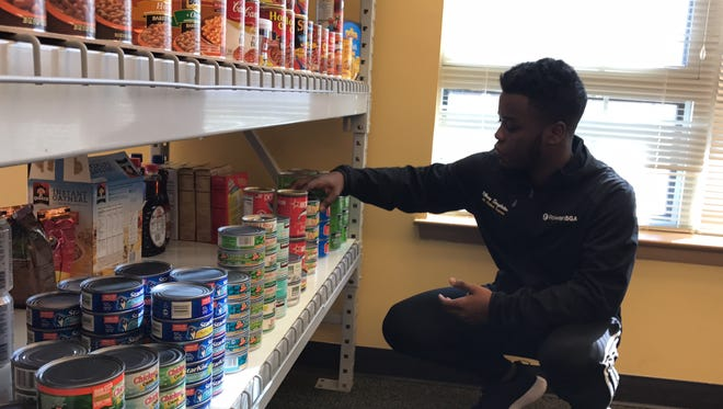 Rbrey Singleon, a founder of Rowan University's student food pantry The SHOP, arranges donated cans.
