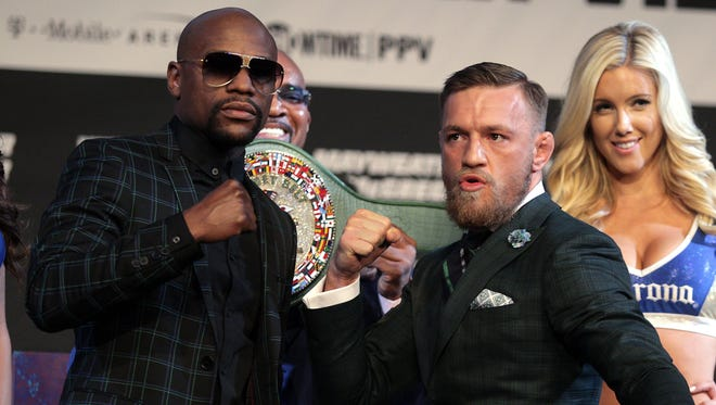 Floyd Mayweather Jr., left, and Connor McGregor pose during a news conference Wednesday promoting their mega fight Saturday in Las Vegas.