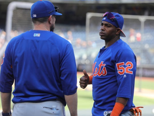 Mets manager Mickey Calloway, left, talks with Yoenis
