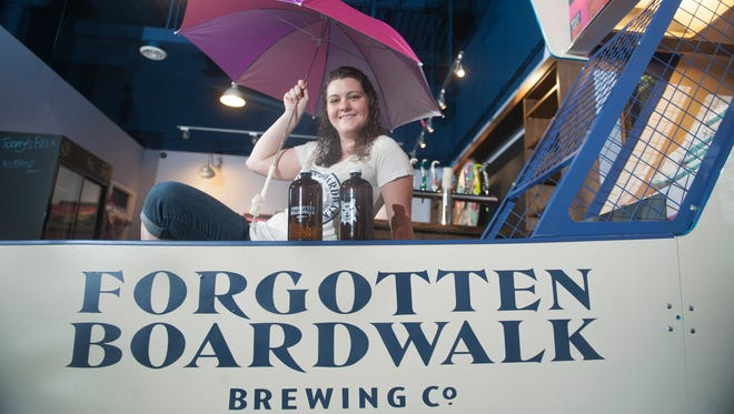 Jamie Queli, owner of Forgotten Boardwalk Brewing Co. in Cherry Hill, sits by a  Skee-Ball machine in her brewery's tasting room.  Playing the machine always means donating some money to a local charity.