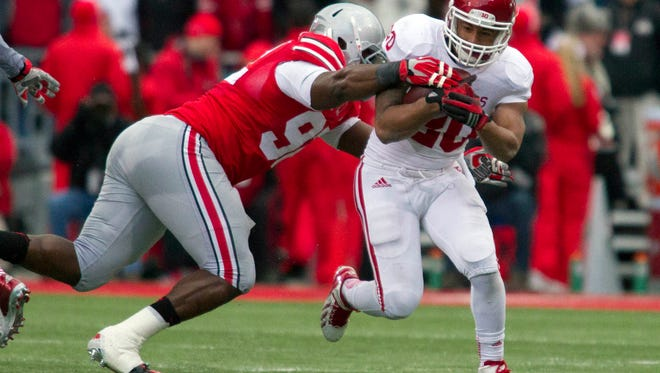 Hoosiers running back D'Angelo Roberts is tackled by Ohio State defensive lineman Adolphus Washington in November of 2013.