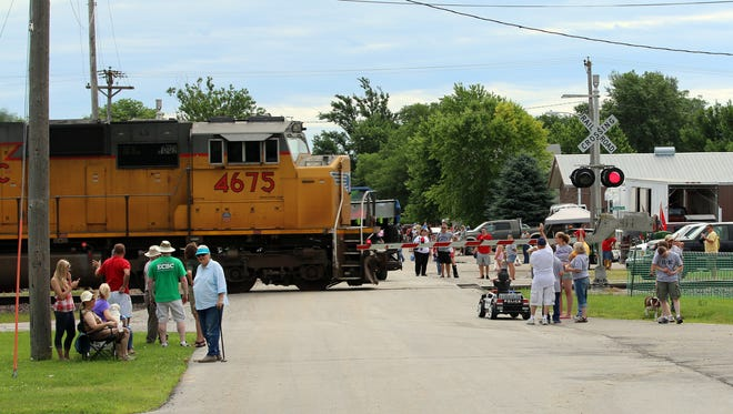 A train carefully crosses Main St. during the parade at the 1st Annual Elkhart City Festival with a fun-fill day featuring a 5K run, a parade, games for the kids, petting zoo, food and craft vendors in the city park, a multiple class truck pull, and live music with an evening concert along Main St.