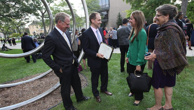 Phil Porter, from left, with his son, William Porter of Porter One Design in Farmington Hills, shows off his certificate to his wife, Steffanie Porter, and mom Valerie Porter after the Goldman Sachs first graduation of the 10,000 Small Businesses in Detroit at Wayne State University on Thursday.
