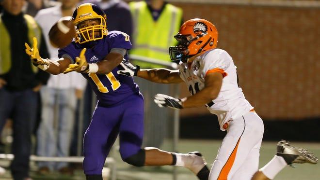 Warren De La Salle's Myles Charley catches a touchdown pass against Birmingham Brother Rice's Joshua Tanksley on Sept. 19, 2014.