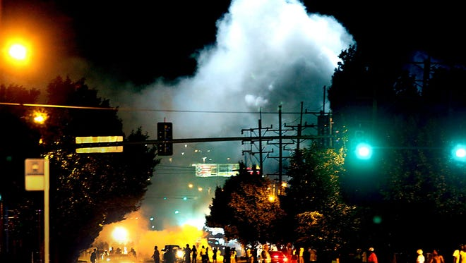 Police officers use tear gas and smoke bombs to clear the street in Ferguson, Mo., on Aug. 13, 2014.