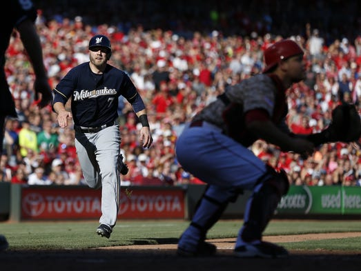 Milwaukee Brewers first baseman Mark Reynolds (7) heads home before being tagged out by the Cincinnati Reds catcher Devin Mesoraco (39) in the seventh inning  at Great American Ball Park.