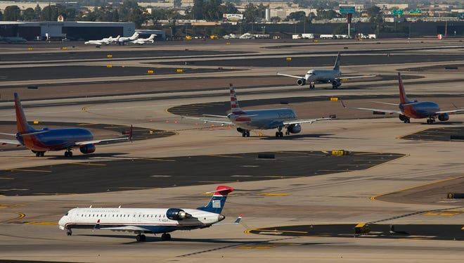 A line of planes sit on the runway waiting for takeoff on the Sunday before Thanksgiving at Phoenix Sky Harbor International Airport in Phoenix on Nov. 23, 2014.