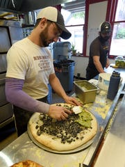 Slyce co-owner, Jeremy Tand, front, spreads guacamole on a half-cooked pizza.
