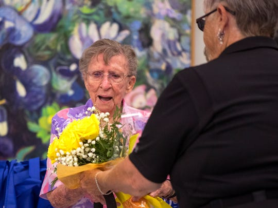 Marcy Mardis (left), 98, receives flowers from Ginger Bryant as she is recognized as the oldest member of the city's senior centers during the annual Forever Young celebration on Wednesday, June 27, 2018 at the Garden Senior Center.