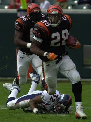 Corey Dillon breaks loose on a 37-yard gain in the third quarter, leaving Denver safety Billy Jenkins in the truf behind him. Dillon set an NFL single-game rushing record with 278 yards.