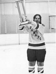 Former Ramapo College ice hockey captain Harry Maynes hoists the league championship cup after the Roadrunners defeated Brooklyn College in the 1975-76 title game.