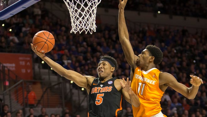 Florida guard KeVaughn Allen shoots a layup past Tennessee forward Kyle Alexander during the first half of Saturday's game in Gainesville, Fla.