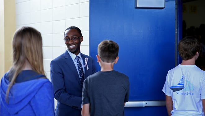 Augustus Raa Middle School Principal Christopher Small greets eight-graders on their way into the gymnasium. Small is the recipient of the 2020 Arts Advocate Award.