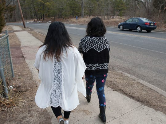 Alberta Juarez (left), Lakewood, walks with her daughter Beverly, 14, on Clover Street in Lakewood near where her son was killed.