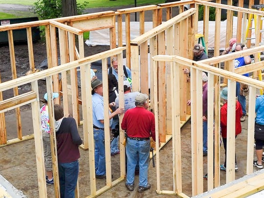 Volunteer assemble the inter walls of a new home being
