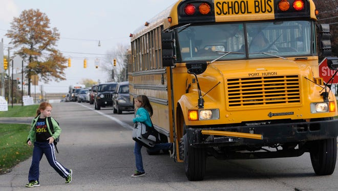 Isabelle Trombly, 7, and Kyleigh Whitmore, 10, get off the bus as cars stop in Port Huron Township along Lapeer Road.
