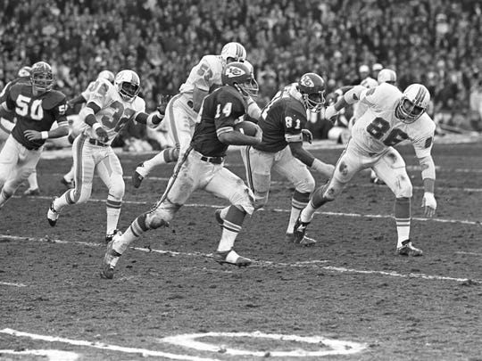 Dec. 25, 1971; Kansas City, MO, USA; FILE PHOTO; Kansas City Chiefs running back Ed Podolak (14) runs back a kickoff and is pursued by Miami Dolphin defenders Hubert Ginn (32), Bob Matheson (53) and VernDen Herder (86) at Municipal Stadium during the 1971 AFC Divisional Playoff game.  Miami won 27-24 in two overtime periods in the longest game ever played in the NFL.  Mandatory Credit: Rod Hanna-USA TODAY Sports