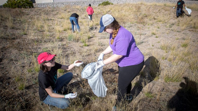 NMSU students Rebecca Archuleta, left, and Mariah Fleming, along with other members of the university's Earth Science Student Organization pick up trash in an empty lot behind the Sonic Drive-In on Foothills Rd as part of the Great American Cleanup, April 9, 2016.