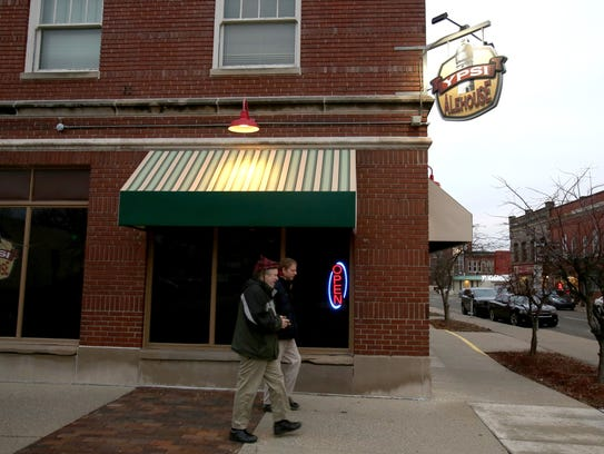 People walk by the outside of the Ypsi AleHouse in