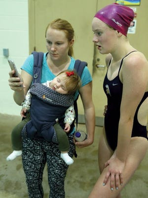 Bainbridge diver Zora Opalka watches a video of her dive with coach Bridget Butler, with her baby Margot Pearl, 4 months, during practice. (LARRY STEAGALL / KITSAP SUN)