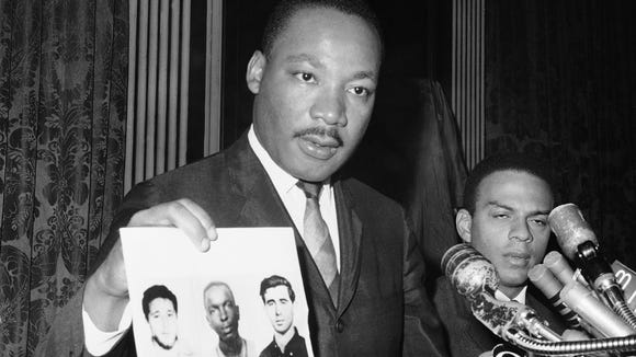 Martin Luther King Jr. holds up the photographs of the three missing civil rights workers in the summer of 1964.