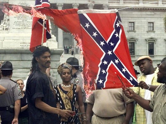 In this May 10, 2000 file photo, Kevin Gray, of the Harriett Tubman Freedom House, watches as the Confederate flag burns during a demonstration in Columbia, S.C., to protest the Confederate flag flying atop the dome of the South Carolina Statehouse. On the left side was a Nazi flag which burned first.